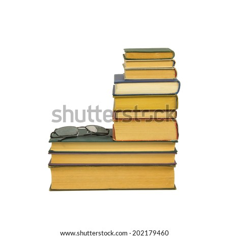 A pile of the old books and glasses isolated on white background - stock photo