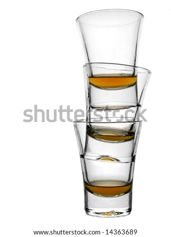 A pile of three almost empty shots of whiskey on white background.