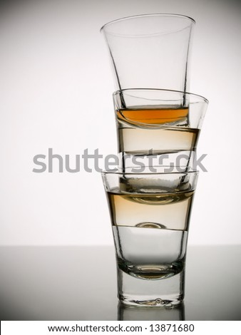 A pile of three almost empty shots of whisky on white background over gray floor - stock photo