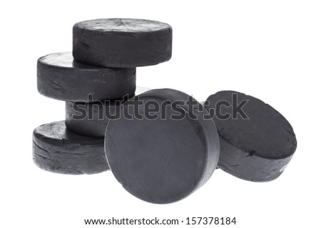 A pile of well used hockey pucks on a white background. - stock photo