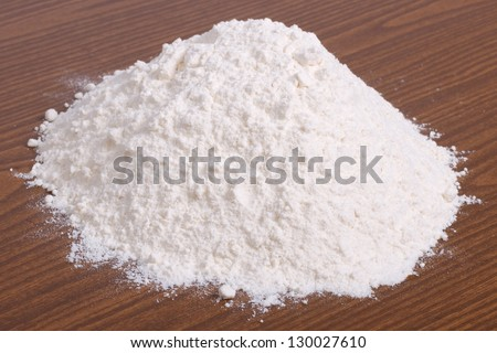 A pile of white wheat flour on a brown wooden table - stock photo