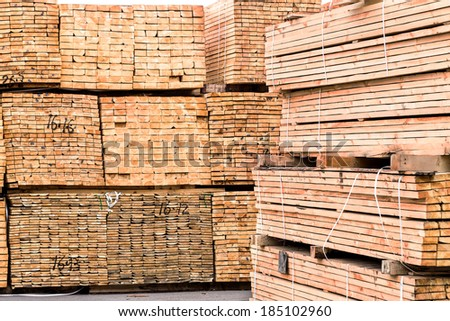 A pile of wood edged boards packed in stacks with tags size parameters for loading cranes and transport the cargo ships in the seaport  - stock photo