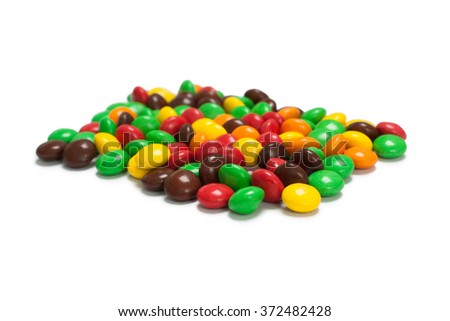 A pile of yellow blue red orange green brown chocolate coated candy - stock photo