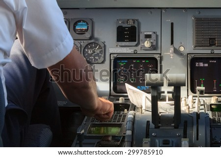 A pilot checking instruments in a plane cockpit - stock photo