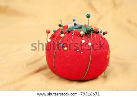 A pin cushion on yellow fabric with needles and a button.