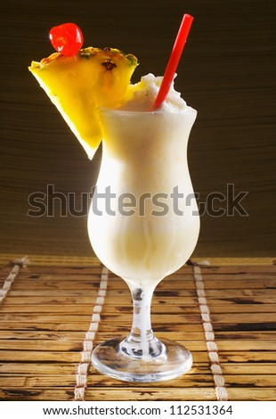 A pina colada cocktail garnished with pineapple on a straw mat