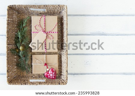 A pine branch and some paper parcels wrapped tied with tags on a tray. A red heart and some christmas gift boxes wrapped with paper kraft and tied with red & white baker's twine. Vintage Style. - stock photo