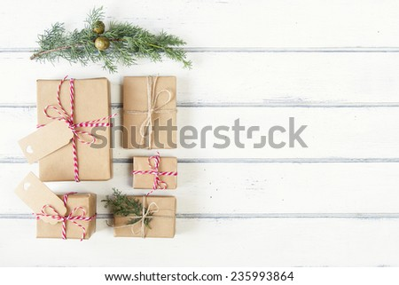 A pine branch and some paper parcels wrapped tied with tags. Some christmas gift boxes wrapped with paper kraft and tied with red & white baker's twine on a white wooden table. Vintage Style. - stock photo