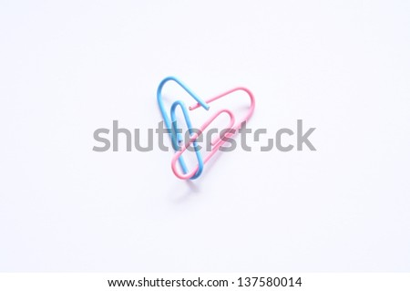 A pink and a blue paperclip forming a heart in a symbol of love and romance.
