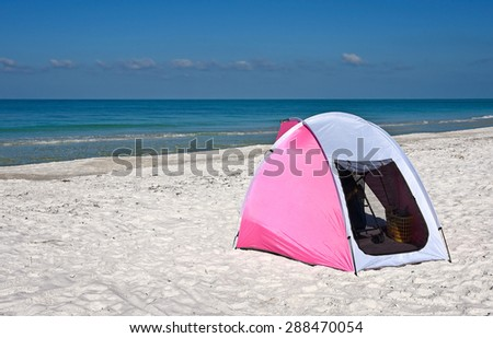 A Pink and White Portable Children's Shelter Beach Tent - stock photo
