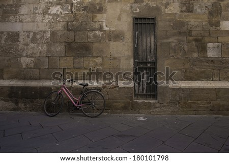 A pink bicycle leans against an old wall by an old door in an Italian Town. / Italian street bicycle in Lucca - stock photo