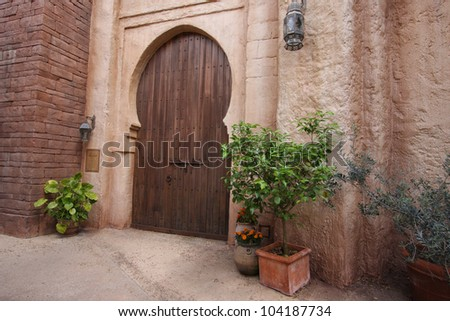 A pink coloured exterior wall with large wooden door, Arab country, travel shot. - stock photo