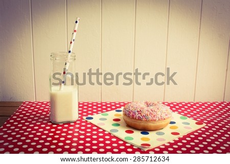 A pink iced donut on polka dots with a glass of milk - stock photo