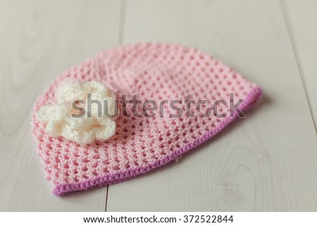 A pink knitted baby hat and a ball of white yarn on a white background.  - stock photo