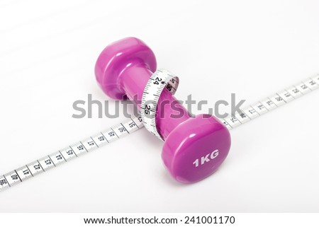 A pink(magenta) dumbbell with tape measure(tape line) on the wood office desk(table) behind white blind. - stock photo