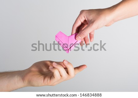 A pink origami heart being passed between man and woman - stock photo