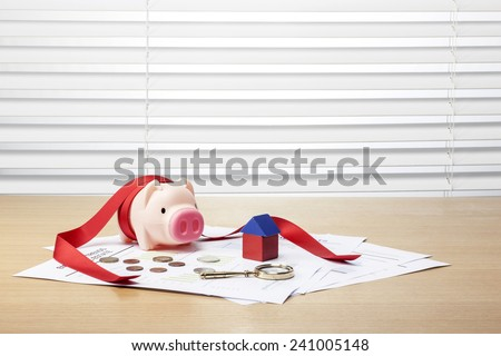 A pink pig coin bank(money box) with house(wood block), coins, magnifier on the graph paper(document, report) on the wood office desk(table) - stock photo