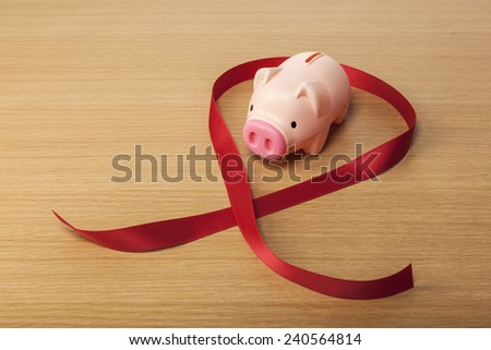 A pink pig coin bank(money box) with red ribbon on the wooden office desk(table). - stock photo