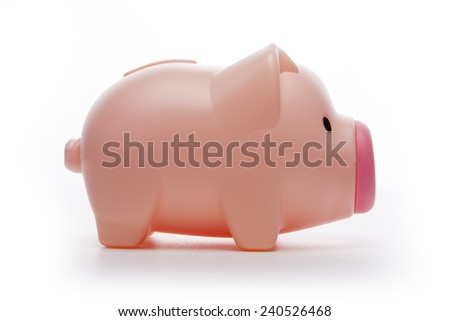A pink pig plastic coin bank isolated white at the studio.