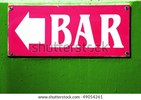 a pink sign of a bar over a green wall