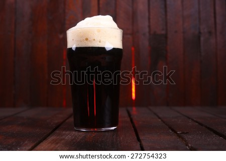 A pint glass full of dark stout ale standing on a wooden table