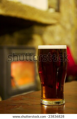 A Pint of Beer on a wodden table and a welcoming fire - stock photo