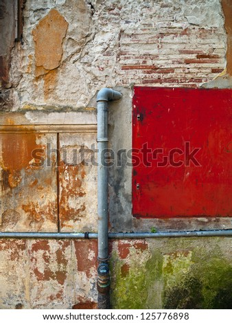 A pipe coming out of a brick wall with a red panel beside it - stock photo