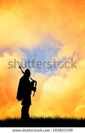 A piper playing the bagpipes at sunset - stock photo