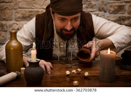 a Pirate is gambling with dice on a medieval table, concept luck and success - stock photo