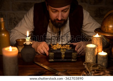 a pirate with a treasure of gold, a lot of candles and old accessories - stock photo