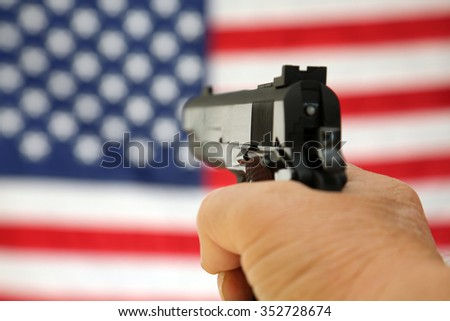 A pistol pointed towards an American Flag, shot with shallow depth of field with the focus on the gun. The American flag is slightly out of focus. 2nd amendment rights. right to bare arms.  - stock photo