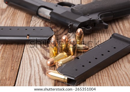 A pistol with two clips and bullets. - stock photo
