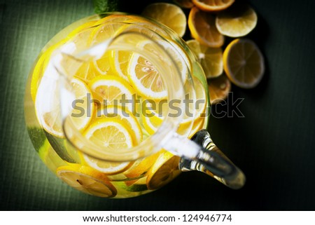 A pitcher of lemonade with slices of lemon and limes.