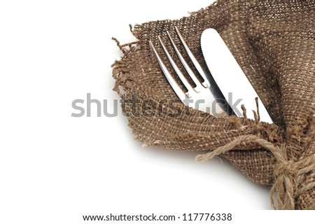 A place setting with silver fork and knife in textile napkin over white with sample text