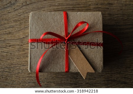 A plain brown cardboard gift box with blank vintage style notched gift tag, tied to a bow with thin red satin ribbon.  Overhead shot on oak wood table. - stock photo