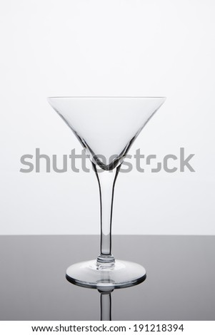A plain, empty martini glass sits atop a reflective surface with a bright white background