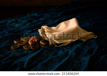 A plain muslin bag with wooden runes spilling out over a sparkling blue cloth. - stock photo