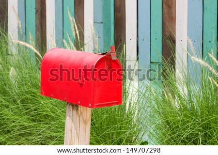 A plain Red Mailbox  in front of some bushes. - stock photo