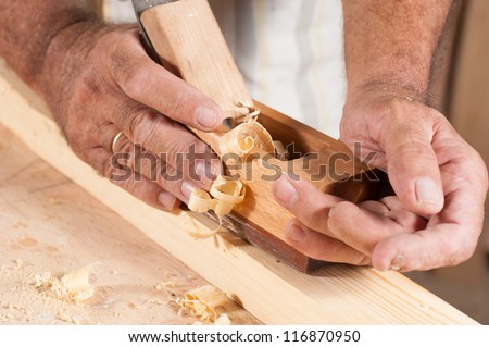 A plane at work in rugged male hands - stock photo
