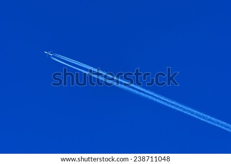 A plane flying on a perfectly blue sky with Vapor Trail - stock photo