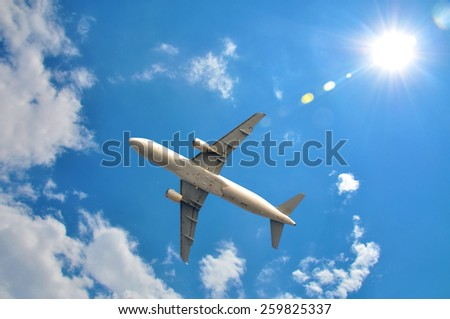 A plane is flying in the sky and sun