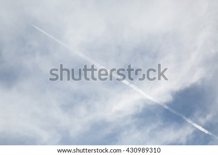 A plane is flying though cloud in the sky.