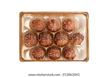a plastic box of milk chocolate sweets isolated on white background