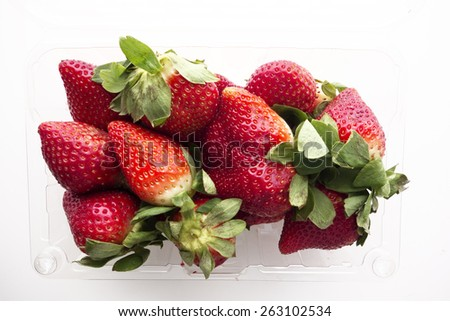 A plastic container of fresh, ripe strawberries. - stock photo