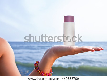 A plastic tube of protective cream on your palm on sea background