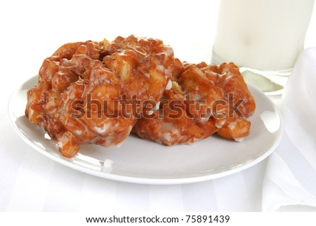 A plate of apple fritters with a glass of cold milk - stock photo