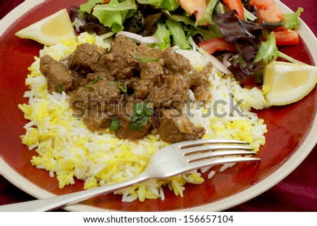 A plate of  beef rogan josh, served with yellow and white rice and a salad. Rogan josh is usually made with lamb, as it is a Hindu dish, but works equally well with beef.