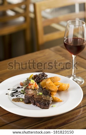 A plate of beef steak to be served with fries, salad and red wine
