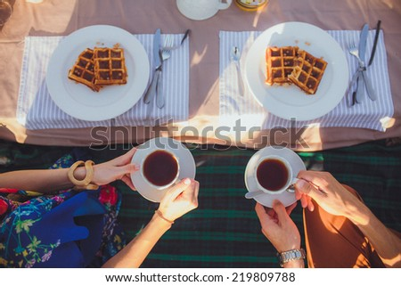 A plate of belgian waffles with fruit and tea cup. Men and girl (couple) hands  preparing to eat it with knife, fork, outdoors - stock photo