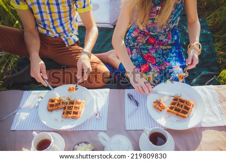 A plate of belgian waffles with fruit and tea cup. Men and girl (couple) hands  preparing to eat it with knife, fork, outdoors